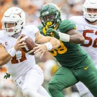 Texas Longhorns quarterback Sam Ehlinger (11) eludes Baylor Bears linebacker William Bradley-King (99) in the second quarter on Saturday. [RICARDO...