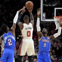 Portland Trail Blazers guard Damian Lillard, center, hits a shot over Oklahoma City Thunder guard Shai Gilgeous-Alexander, left, and center...