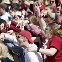 Oklahoma fans cheer during the Red River Showdown college football game between the University of Oklahoma Sooners (OU) and the Texas Longhorns...