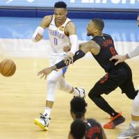 Damian Lillard (0) reaches for the ball beside Russell Westbrook (0) during Game 4 in the first round of the NBA playoffs between the Portland...