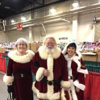 Mr. and Mrs. Claus, portrayed by Larry and Daneta Blair, pose with Mary Blankenship Pointer, secretary/treasurer of the annual Red Andrews...