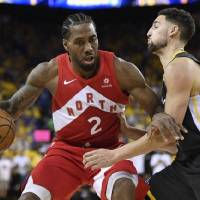 Toronto Raptors forward Kawhi Leonard, left, handles the ball while Golden State Warriors guard Klay Thompson defends during Game 6 of the NBA...
