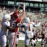 OU's Austin Stogner (18) catches a touchdown pass in overtime over Texas defensive Jalen Green (3) during the Sooners' 53-45 win on Oct. 10 in...
