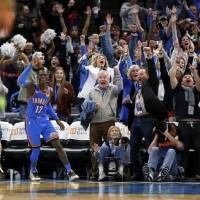 Dennis Schroder (17) celebrates, along with Thunder fans, his game-tying basket to force overtime in an eventual 139-127 win Friday night against...