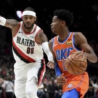 Oklahoma City Thunder guard Shai Gilgeous-Alexander, right, drives to the basket on Portland Trail Blazers forward Carmelo Anthony during Sunday...