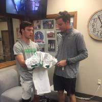 McGuinness' Carter Pierce (left) takes a signed jersey to Southwest Covenant. Pierce wears No. 14, the same number Peter Webb, who died Sunday...