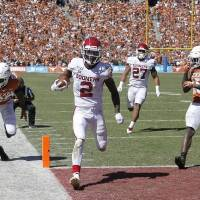 CeeDee Lamb (2) scores a touchdown in front of Texas defensive backs B.J. Foster (25) and Chris Brown (15) during Oklahoma's 34-27 win at Cotton...