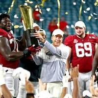 Alabama coach Nick Saban and offensive lineman Alex Leatherwood (70) celebrate with the College Football Playoff national championship trophy...