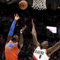 Oklahoma City Thunder guard Luguentz Dort, left, shoots the ball over Portland Trail Blazers forward Nassir Little during Sunday night's game in...