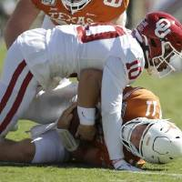 Oklahoma safety Pat Fields (10) brings down Texas quarterback Sam Ehlinger (11) during the Red River Showdown college football game between the...