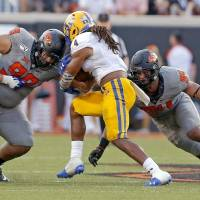 Oklahoma State's Sione Asi (99) makes a tackle in a game last season. [Sarah Phipps/The Oklahoman]