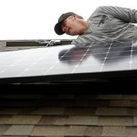 Jeremy Rains, with Solar Power of Oklahoma, lines up a solar panel on the roof of Brian Bennett's home in Edmond. [BRYAN TERRY/THE OKLAHOMAN]