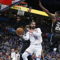 Oklahoma City's Steven Adams (12) pass the ball has he is defended by New Zealand Breakers' Ater Majok (33) and Sek Henry (22) during the NBA...