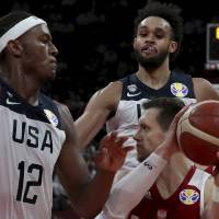 United States' Derrick White, top right looks on as United States' Myles Turner tries to block Poland's Mateusz Ponitka during a consolation...
