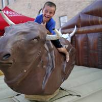 Layne Rainey, 5, laughs as he rides a mechanical bull during Rock the Route, a red dirt country music festival, in downtown Yukon, Okla.,,...
