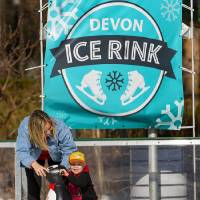 Emma Petry helps her son Troy, 4, as they try to keep their footing on the ice while skating at the Devon Ice Rink in Oklahoma City, Okla. on...
