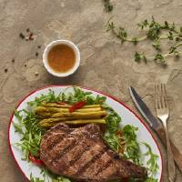 Grilled rib-eye is accented with local arugula and a glaze made from Oklahoma-made ingredients. [Photo provided]