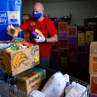 Skyline Urban Ministry food resource manager, Nicholas Hoey loads food boxes with cookies donated by Girl Scouts Western Oklahoma and the United...