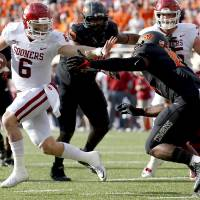 Oklahoma's Baker Mayfield (6) gets by Oklahoma State's Justin Phillips (19) on the way to a touchdown in the second quarter during the Bedlam college football game between the Oklahoma State Cowboys (OSU) and the Oklahoma Sooners (OU) at Boone Pickens Stadium in Stillwater, Okla., Saturday, Nov. 4, 2017. Photo by Sarah Phipps, The Oklahoman