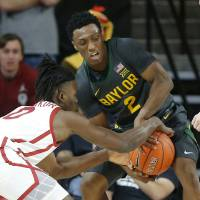 Oklahoma's Victor Iwuakor (0) fights for the ball with Baylor's Devonte Bandoo (2) during a men's NCAA basketball game between the University of...