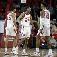 Oklahoma's Alondes Williams (15), Jamal Bieniemy (24) and Kristian Doolittle (21) celebrate during an NCAA basketball game between the University...