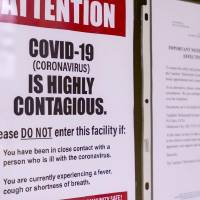 Signs that are posted about the Coronavirus on the doors of the Oklahoma State Department of Education in Oklahoma City, Okla. on Monday, March 16,...