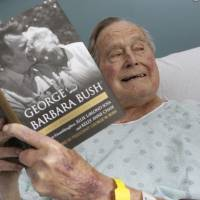 This file photo provided by Office of George H. W. Bush shows a photo of former President George H.W. Bush that was tweeted on Friday, June 1, 2018, from his hospital bed while reading a book about himself and his late wife in Biddeford, Maine. Bush is celebrating his 94th birthday in Maine. He is relaxing at his home in Kennebunkport on Tuesday, June 12, eight days after being released from the hospital where he was treated for low blood pressure. (Paul Morse/Office of George H. W. Bush via AP, File)