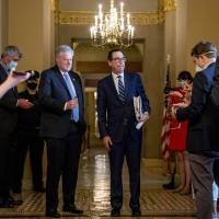 Treasury Secretary Steven Mnuchin, right, accompanied by White House chief of staff Mark Meadows, left, takes a question from a reporter following...