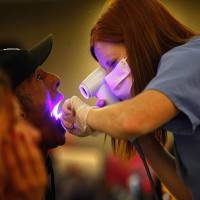"BRIGHTON, CO - SEPTEMBER 11:  Dental hygiene student Audrey Rayniak gives an oral cancer screening to Kevin Smith at a free dental clinic on September 11, 2009 in Brighton, Colorado. Smith, an unemployed carpenter for a year, said he has been unable to afford dental insurance or pay to have dental work done. ""I need a new mouth, and it would have cost me ten grand,"" he said. The third annual Colorado Mission of Mercy clinic aims to treat as many as two thousand low-income people during the two-day event. Some 750 volunteers, including almost 150 dentists, donated their time to help uninsured patients in need of dental care. With millions of the recently unemployed having lost dental coverage, organizers expect many more people to come than can be treated during the event.  (Photo by John Moore/Getty Images)"
