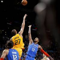 Oklahoma City's Paul George (13) shoots the go ahead basket in double overtime over Utah's Rudy Gobert (27) during the NBA game between the...