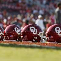 OU helmets sit on the field as players warm up before a college football game between the Oklahoma Sooners (OU) and South Dakota Coyotes at Gaylord...