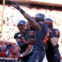 Oklahoma State celebrates a 92-yard touchdown run by Chuba Hubbard (30) in the third quarter during the college football game between the Oklahoma...