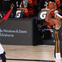Oklahoma City Thunder rookie forward Darius Bazley (right) makes a 3-point basket  over Washington Wizards forward Isaac Bonga during the first...