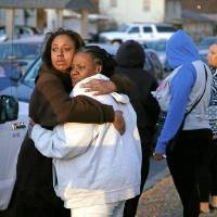 Adrienne Nation (left) comforts Kim Tyes at the scene of a homicide in which Tyes's son was allegedly shot by his girlfriend on East Young Place in Tulsa, Okla., taken on February 18, 2016, Nation is the cousin of the victim. JAMES GIBBARD/Tulsa World