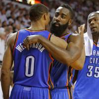 Oklahoma City's James Harden, center, hugs Russell Westbrook, as Kevin Durant watches during the final minutes of Game 5 of the NBA Finals between...