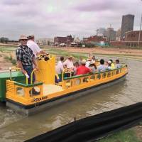 Water taxi trainees are shown making a trial run through a desolate field that is now Lower Bricktown and home to restaurants, shops, movie...