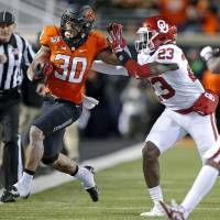 Oklahoma's DaShaun White (23) pushes Chuba Hubbard (30) out of bounds in the fist quarter during the Bedlam college football game between the...