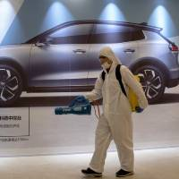 In this Feb. 12, 2020, photo, a worker disinfects a mall near an advertisement for a car in Beijing, China. Automakers are gradually reopening...