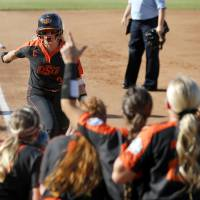 Oklahoma State's Samantha Show (3) celebrates after hitting a home run in the first inning of the third game of the Women's College World Series...