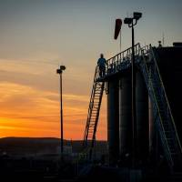 A worker checks tanks at a field location. Abundant supplies of crude oil and natural gas have depressed prices, causing a slowdown in drilling...