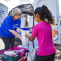Oklahoma City Public School Cafeteria Supervisor Ramona Andruchow helps Yoselin Ramirez, 6, pick out items for her lunch through the  Summer...