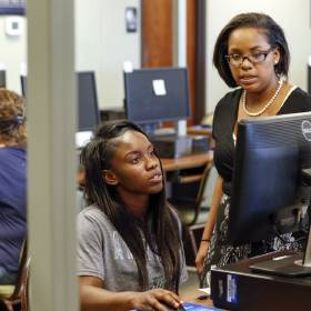 Inazereth Geionety, right, helps Shaquez Johnson conduct a job search on a computer at an OK...
