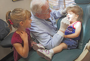 Photo - Dr. J Dean Robertson checks the teeth of Kylie Davis, 2, as her older sister, Kimberly, 4, watches. Photo by Chris Landsberger, The Oklahoman