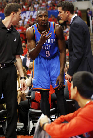 Photo - Oklahoma City's Serge Ibaka (9) talks with the Thunder staff before leaving the floor after injuring himself during Game 6 of the Western Conference semifinals in the NBA playoffs between the Oklahoma City Thunder and the Los Angeles Clippers at the Staples Center in Los Angeles, Thursday, May 15, 2014. Photo by Nate Billings, The Oklahoman
