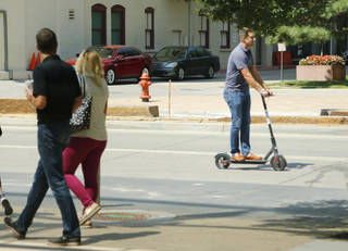 A person riding a Bird scooter goes north on Robinson in downtown Oklahoma City on Friday. [Photo by Doug Hoke,The Oklahoman]
