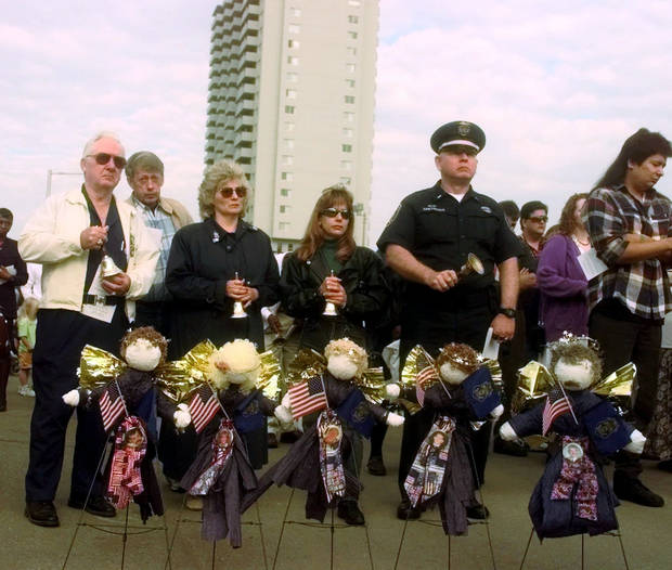 Friends and relatives of law enforcement officers killed in the Alfred Murrah Federal Building car bomb explosion stand behind memorial wreaths Sunday, April 19, 1998, during a memorial ceremony marking the third anniversary of the bombing. (AP Photo/Jerry Laizure)