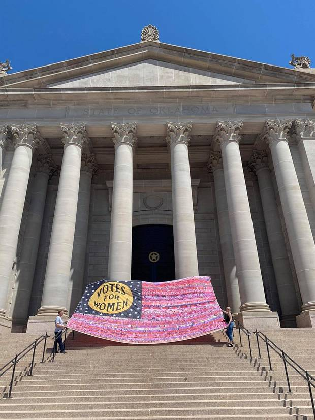 "Oklahoma City artist Marilyn Artus has been working since 2017 on ""Her Flag,"" a multiyear, cross-country collaborative art project to celebrate the 100th anniversary of the 19th Amendment to the U.S. Constitution. Artus and her family took the flag to the Oklahoma Capitol steps to photograph the progress on April 25, after she sewed on the 30th of the flag's 36 planned stripes. [Provided/Marilyn Artus]"
