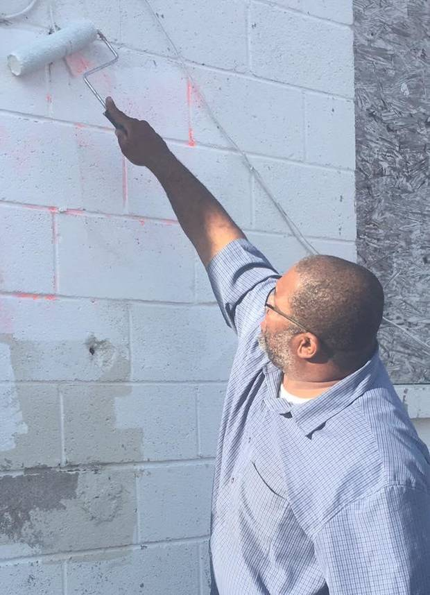 Saad Mohammed, director of Islamic news and information for the Islamic Society of Greater Oklahoma City, paints over anti-Muslim messages and slurs that vandals wrote on the exterior of a Muslim-owned grocery story in northwest Oklahoma City. [Photo provided]