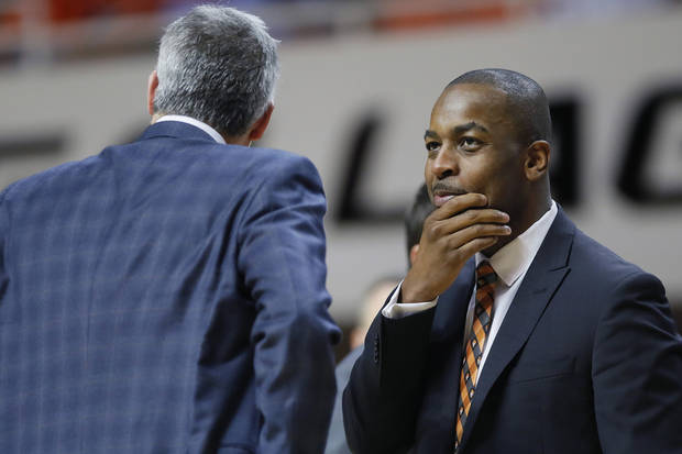 Mike Boynton talks with assistant Scott Sutton during Wednesday's game against Texas Tech. [Bryan Terry/The Oklahoman]