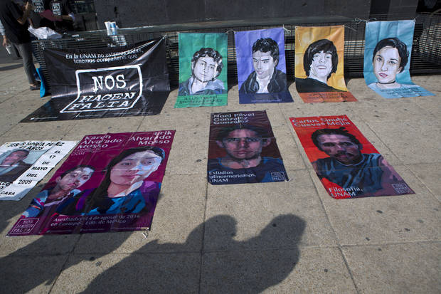 "Passerby pause to look at posters showing some victims of the Mexican drug war, on the 10th anniversary of its start, at the Monument  for the the Mexican Revolution, in Mexico City, Sunday, Dec. 11, 2016. Ten years after Mexico declared a war on drugs, the offensive has left some major drug cartels splintered and many old-line kingpins like Joaquin ""El Chapo"" Guzman in jail, but done little to reduce crime or violence in the nation's roughest regions.(AP Photo/Rebecca Blackwell)"